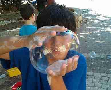 ילד חמוד יוצר בועת סבון ענקית בידיים