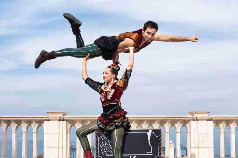 אמנית קרקס מרימה בחור מעל הראש במופע קרקס